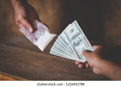 Hand of addict man with money buying dose of cocaine or heroine, close up of addict buying dose from drug dealer, drug trafficking, crime, addiction and sale concept,