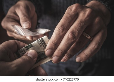 Hand of addict man with money buying dose of cocaine or heroine or another narcotic from drug dealer. Drug abuse and traffic concept, toned