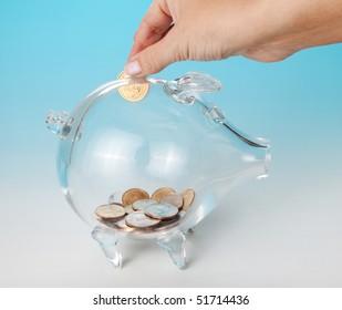 Hand adding a dollar to a glass piggy bank