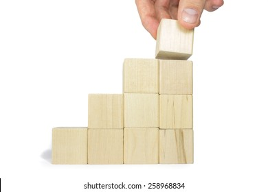 A Hand Adding The Last Wooden Block To A Stairs Build Out Of Wood Blocks
