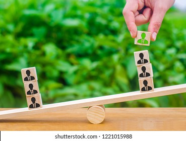 The hand adds a cube with the image of the employee to the stack on the scales. The concept of hiring employees and the appointment of the leader and leader of the team. Business management personnel.