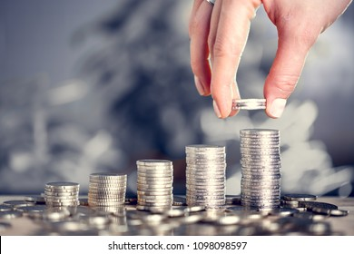 Hand adds money to the pile. Concept of banking, exchange rates, savings and expenses.