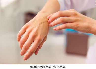 Hand with adhesive plaster that covering a slight injury, close-up