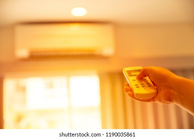 hand adjust AC temperature with remote control to wall type air conditioning home cooling system in very hot summer day