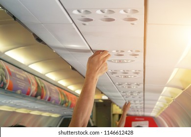 hand up to adjust console panel; the air condition, light / lamp above the low cost airline seat.  above seat while on board of an aircraft,selective focus.