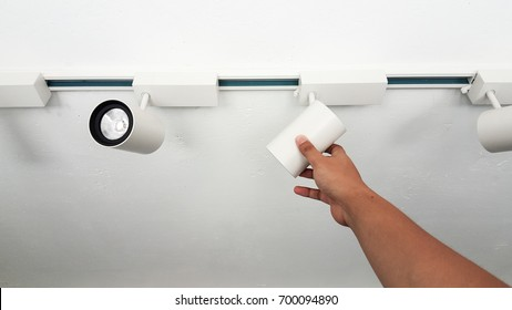 Hand adjust LED downlight lamp on white ceiling.