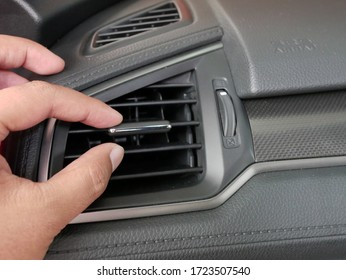 hand adjusting the air conditioner button in mordern car.