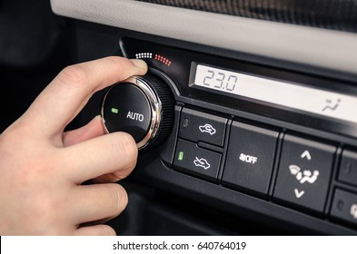 Hand adjusting the internal temperature of the car by turning the temperature control knob.