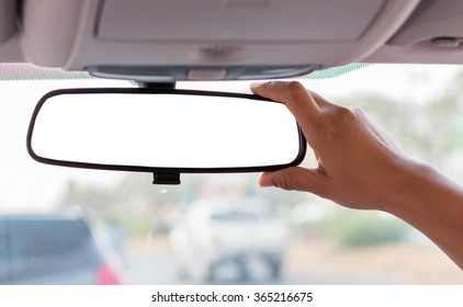 Hand adjusting rear view mirror.