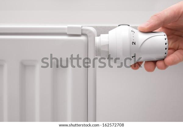 hand adjusting the temperature of heating radiator