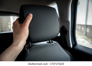 Hand adjusts leather headrest in car interior.