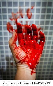 Hand of adult Asian woman who is depressed and covered with fresh blood against wet bathroom tiles wall. Horror halloween or Violence Homicide murder or Domestic violence concept.