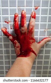 Hand of adult Asian woman who is depressed and covered with fresh blood, holding on wet bathroom tiles wall. Horror halloween or Violence Homicide murder or Domestic violence concept.