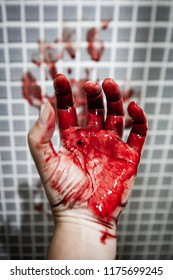 Hand of adult Asian woman who is depressed and covered with old and dried out blood against wet bathroom tiles wall. Horror halloween or Violence Homicide murder or Domestic violence concept.