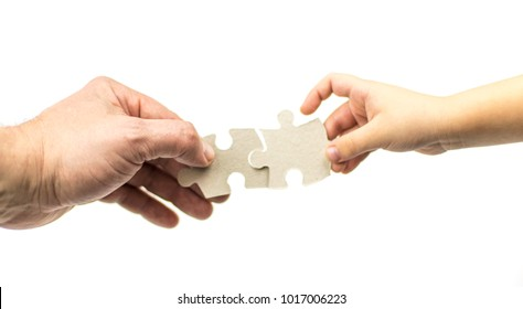 Hand of an adult and child with puzzles on a white background. Isolated. The concept of mutual understanding with the child.