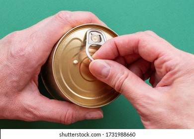 The hand of an adult holds a can of canned food, the second hand pulls the key. Top view on green background, close-up