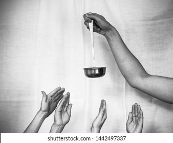 The hand of an adult holds a ladle, children's hands reach for it.
