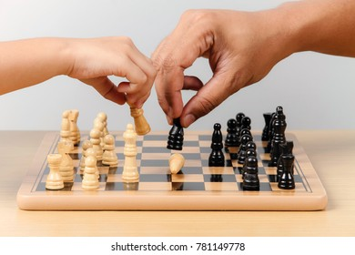 A hand of an adult and kid playing chess together