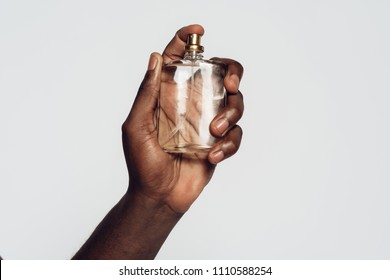 Hand of Afro American man holding perfume. Isolated on white background. Studio portrait.