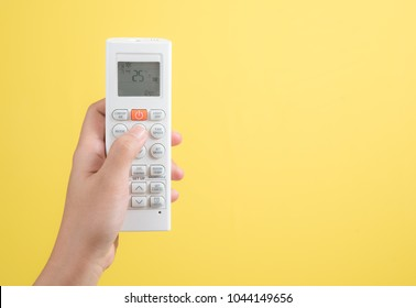 Hand with air conditioner remote control on yellow background,adjust air conditioner to 25 degrees celsius