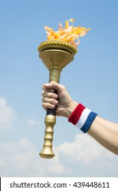 Hand of an American athlete wearing USA red, white, and blue colors sweatband holding stylized flame against tropical blue sky