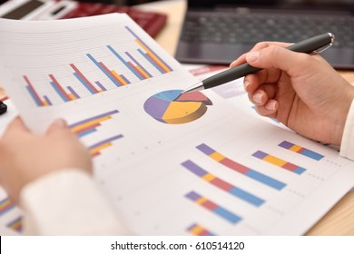 Hand analyzing income graphs and charts. Business analysis and strategy concept.