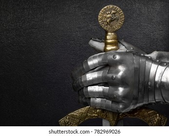 A hand in an ancient knight's glove holds a beautiful sword on a dark background. High resolution studio image.