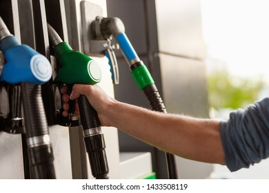 Hand of anonymous customer taking fuel nozzle from pump while visiting self-service gas station on sunny day