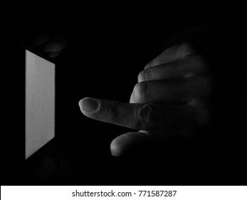 A hand of anonymous internet user holding a smartphone in the darkness and finger tapping on the screen