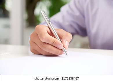 Hand of anonymous man holding nice pen and writing on paper sheet