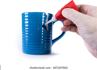 Hand applying glue to a hole in an almost repaired cup