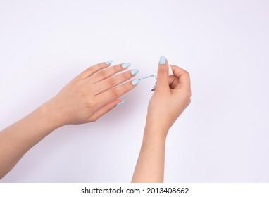 Hand applying nail polish beauty nails light blue  - Shutterstock ID 2013408662