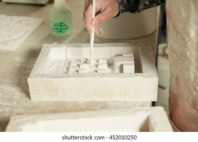 A hand applying a thin layer of plaster on rectangular mold using a paintbrush
