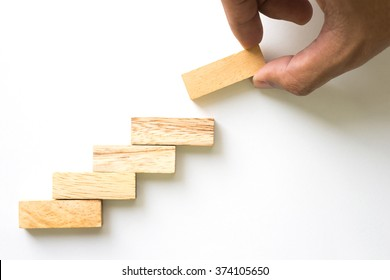 Hand aranging wood block stacking as step stair. Business concept for growth success process.