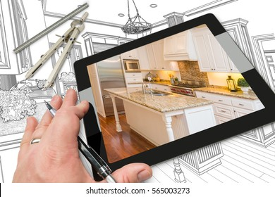 Hand of Architect on Computer Tablet Showing Photo of Kitchen Drawing Behind with Compass and Ruler.