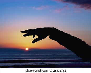 a hand and an arm as a black silhouette bends high against the still blue evening sky over the sun, which is just sinking into the sea. Backlit Low