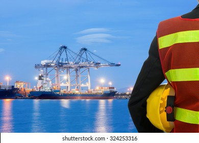 Hand or arm of businessman engineering manager wearing safety clothing hold yellow plastic helmet in front of cargo transportation port during import or export loading containers box