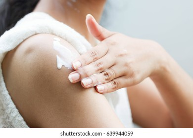 Hand and arm of lady that doing apply whitening lotion on tantalum of her skin