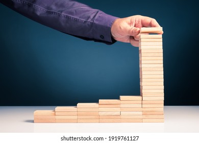 Hand arrange the step stairs wood blocks by adding the last step higher than usual. Compound interest. High return in long term savings, insurance or business progress concept