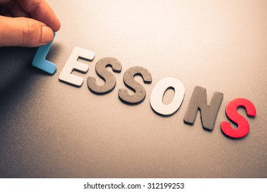 Hand arrange wood letters as Lessons Word