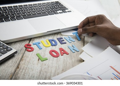 Hand arrange wood letters as student Loan word