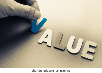 Hand arrange wood letters as Value word