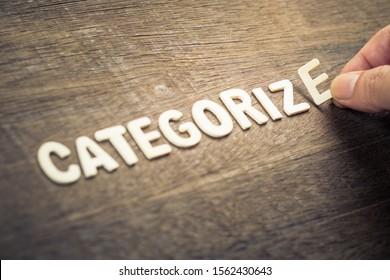 Hand arrange wooden alphabets as Categorize word on wood background