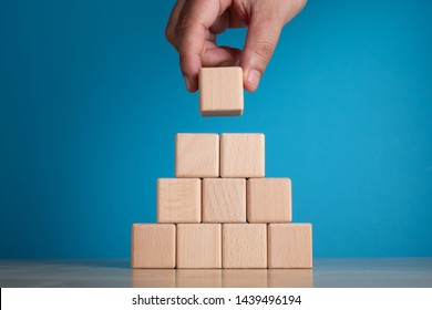 Hand arranging block on blue background. Business concept on progress or building something.