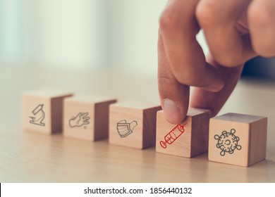hand arranging on wooden cube of covid-19 spread to 2021 years which hope to found vaccine of corona virus, choose the right vaccine to treat the patient to get well better and delivery around world