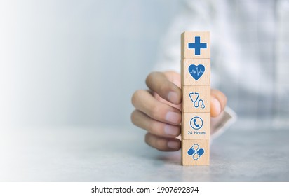 Hand arranging wood block with healthcare medical icon. Health insurance concept.