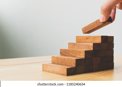 Hand arranging wood block stacking as step stair. Ladder career path concept for business growth success process