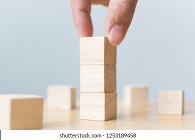 Hand arranging wood block stacking on top with wooden table. Business concept for growth success process