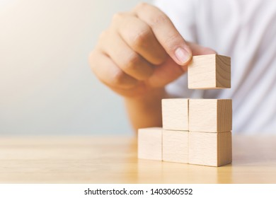Hand arranging wood block stacking as step stair on top. Business concept for growth success process