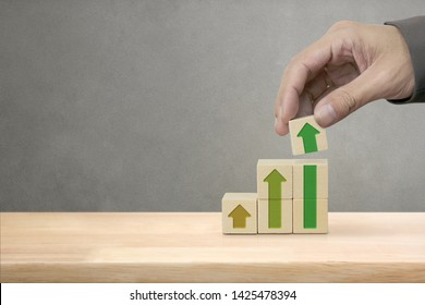Hand arranging wood block stacking as step stair with arrow up, Ladder career path for business growth success process concept.
